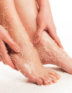 Hands exfoliating feet with chemical exfoliation.